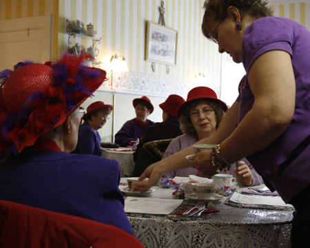 The drinks are served to the group of Red Hat Society women as they are looking through the menu to decide what they will eat.