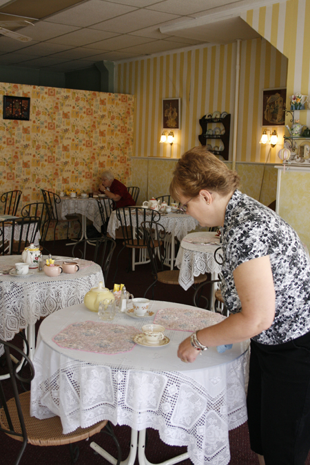 JoDel cleans and readies the tables for the customers that will come in to the café for lunch. Different teaspoons and teacups are placed on each table to give the settings their own individual feel.